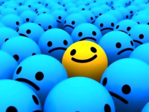 positive thinking-smile in crowd of frowns